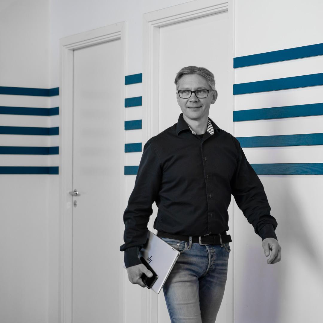 Porträttfoto: Rickard Björkman i svart skjorta och jeans, på språng med dator och mobil i handen.