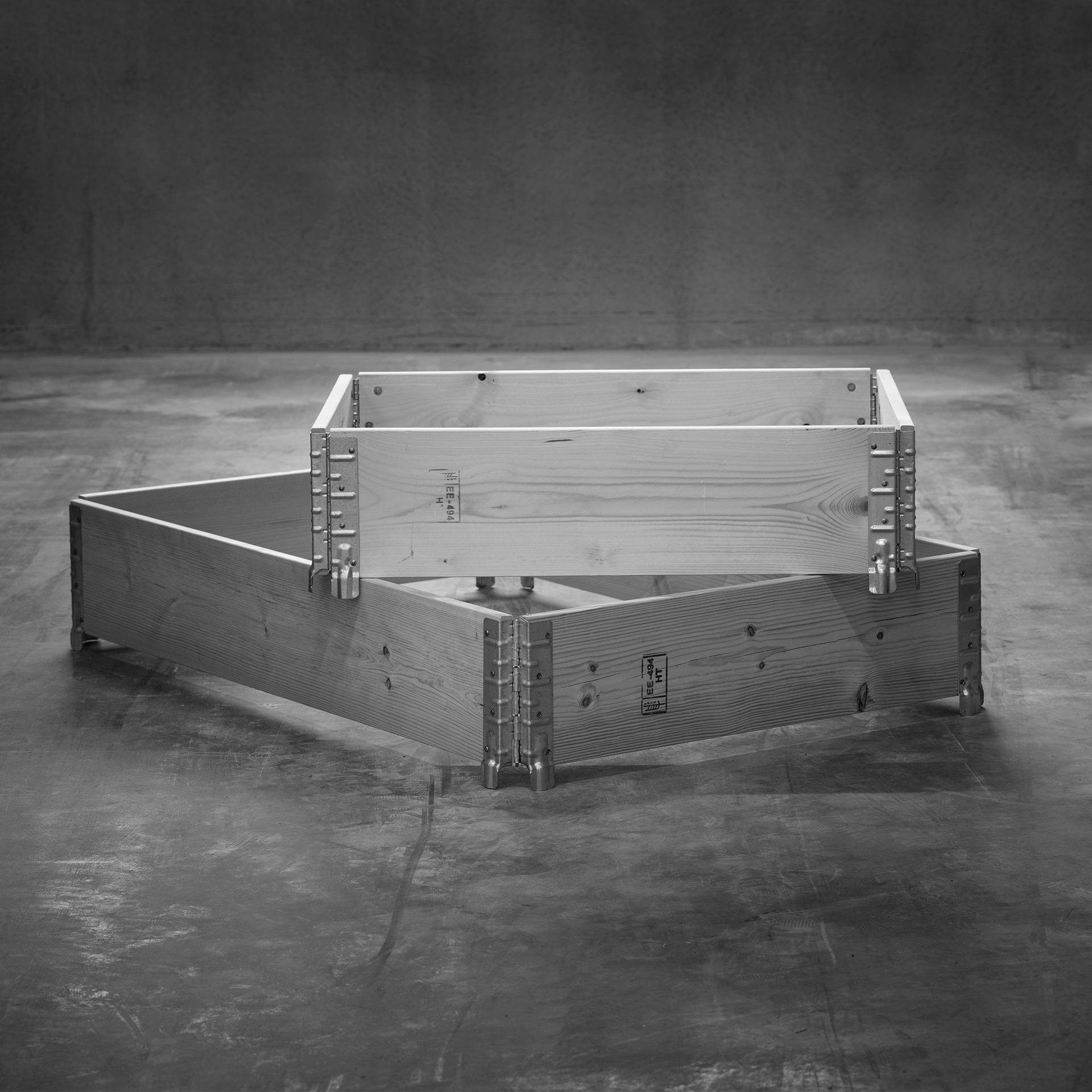 Pallkrage för halvpall ovanpå en pallkrage för helpall, stående på ett betonggolv.